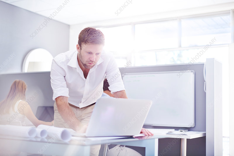 Architect using laptop in sunny office