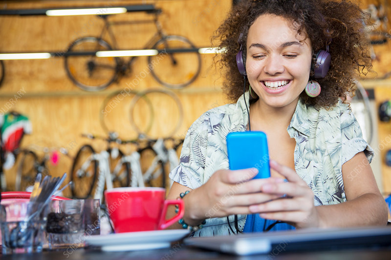 Smiling woman texting in bike shop