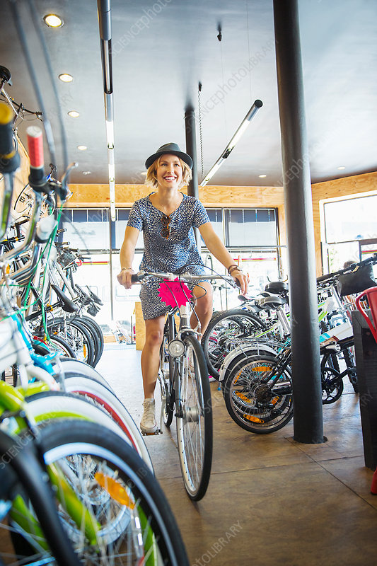 Smiling woman riding bicycle in bike shop