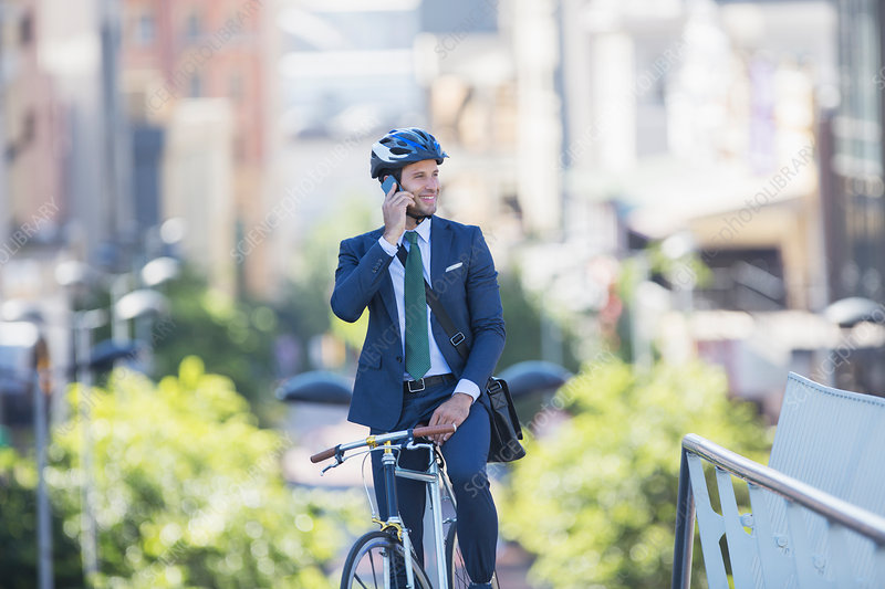 Businessman sitting on bicycle