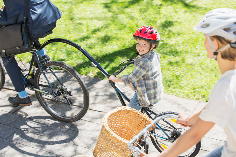 Boy riding tandem bicycle with father