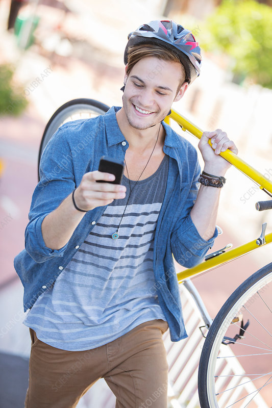 Young man carrying bicycle and texting