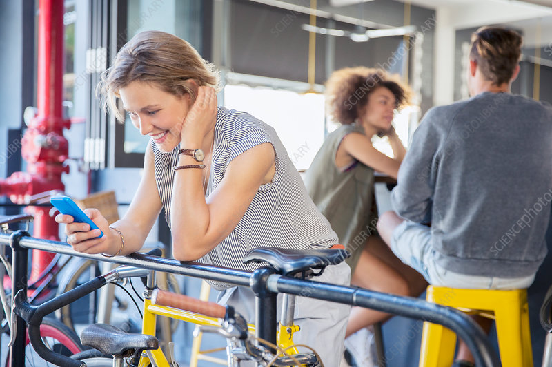Woman texting at railing above bicycle