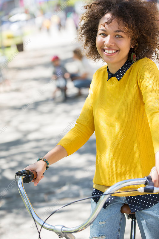 Portrait smiling woman on bicycle in park