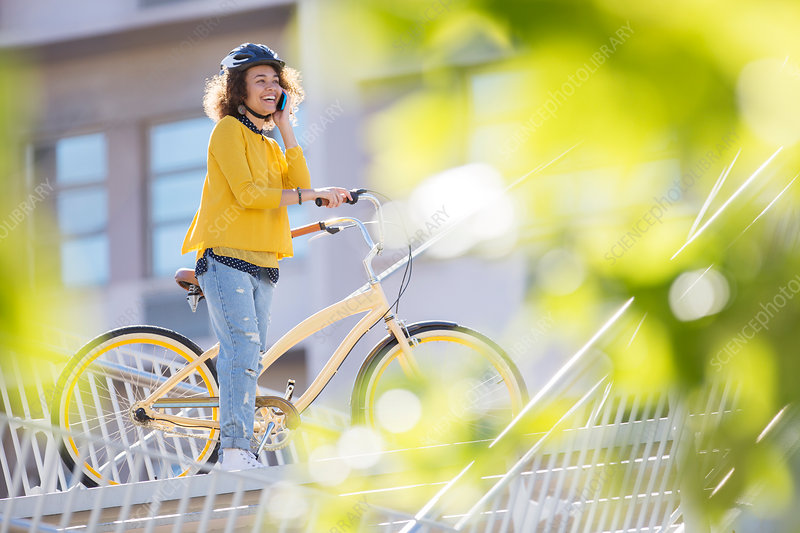 Smiling woman talking on bicycle in city