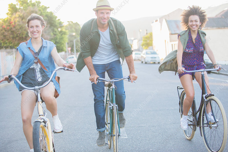 Smiling friends riding bicycles on street