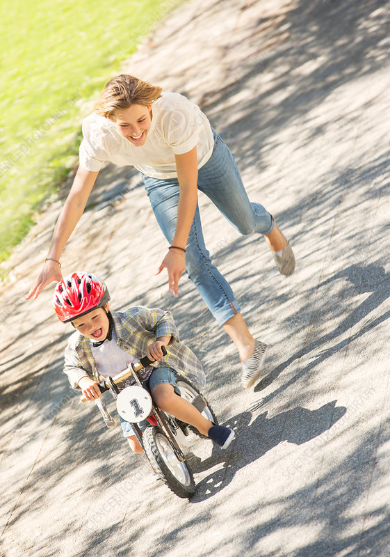 Mother pushing son on bicycle