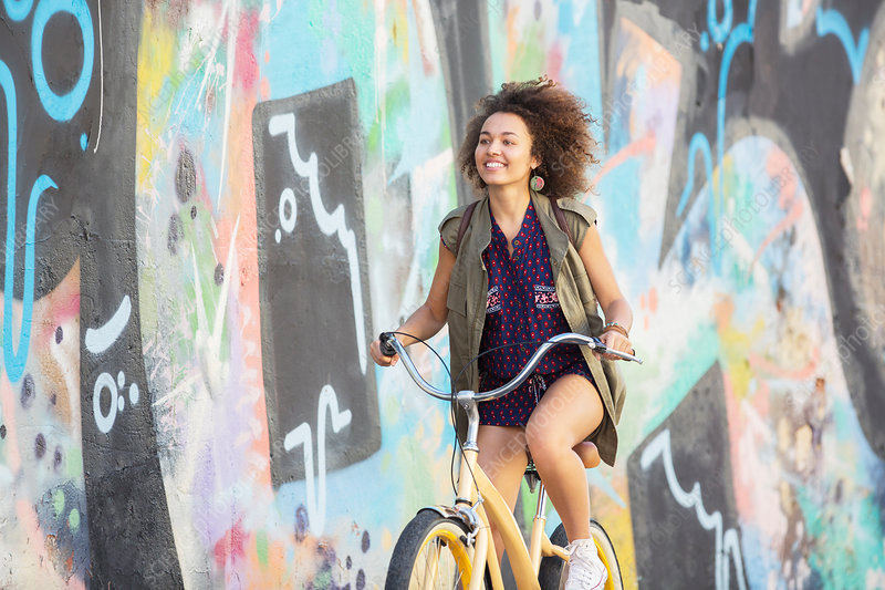 Smiling brunette woman riding bicycle
