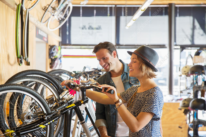 Couple looking at price tags on bicycles