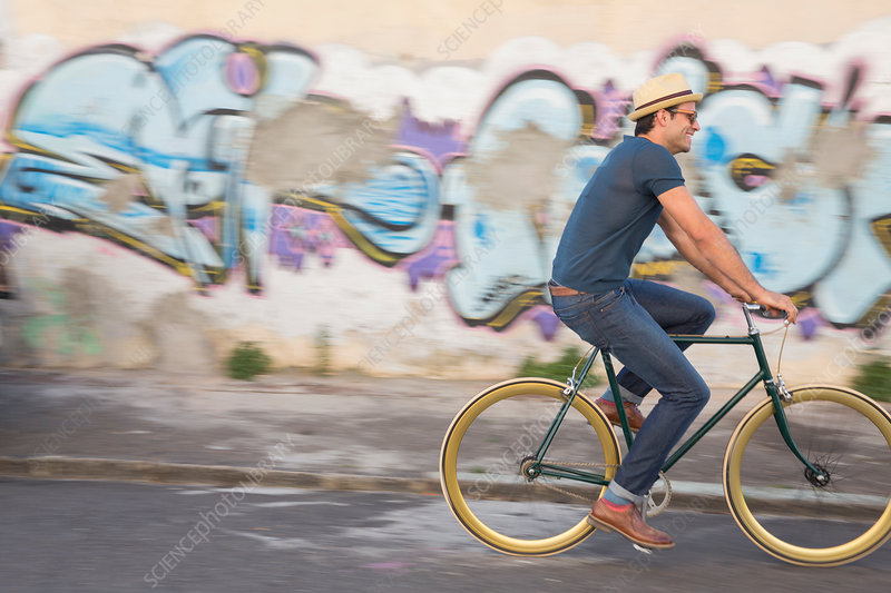 Hipster man riding bicycle on road