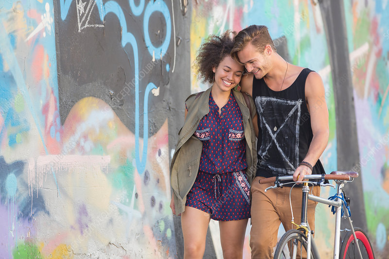 Couple hugging and walking with bicycle
