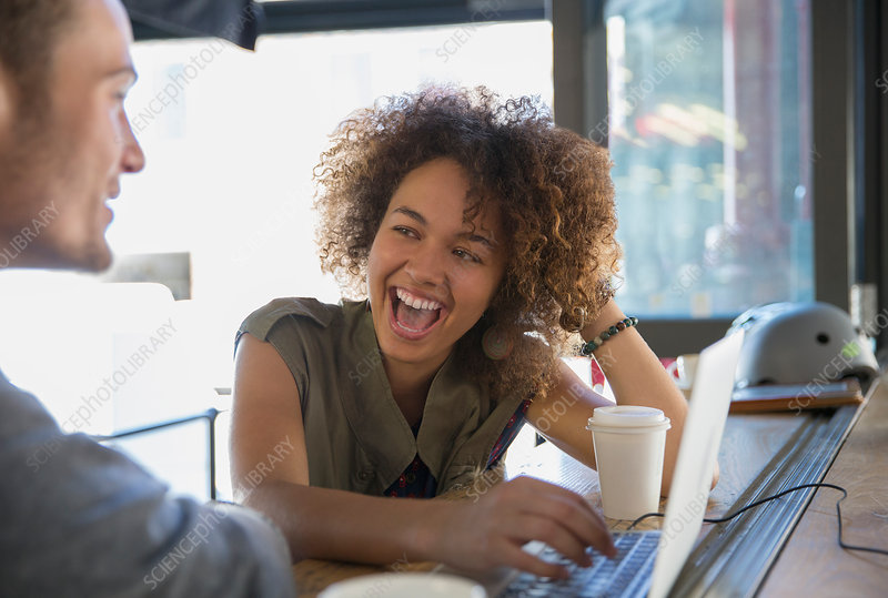 Enthusiastic woman laughing in cafe