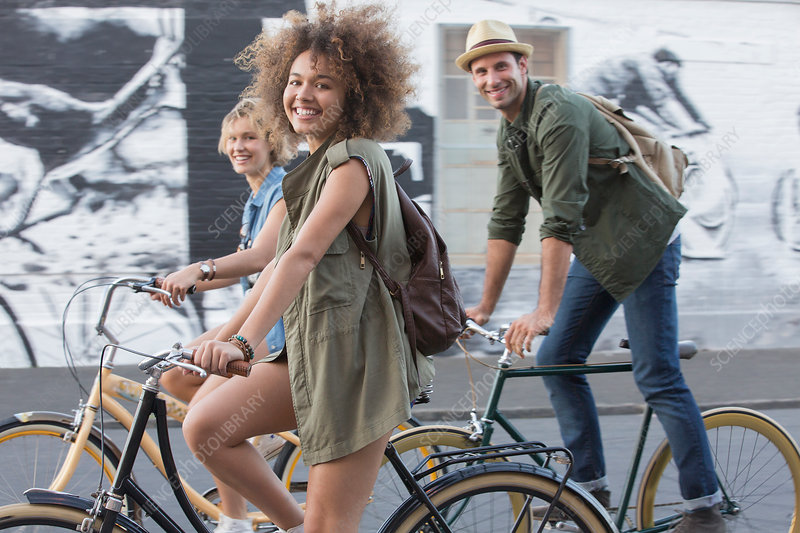 Friends riding bicycles on urban street