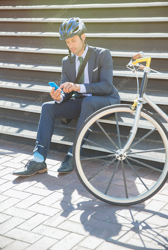 Businessman texting next to bicycle