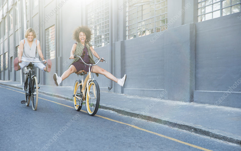 Playful women coasting on bicycles
