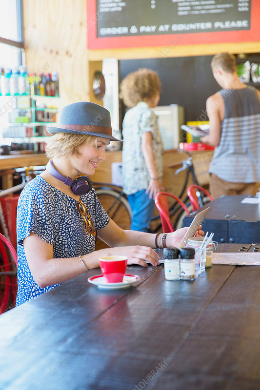 Woman in hat using digital tablet at cafe