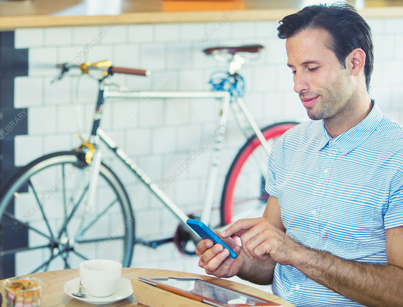 Man texting near bicycle in cafe