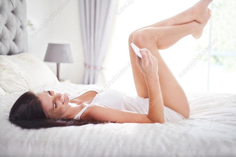 Woman laying on bed texting
