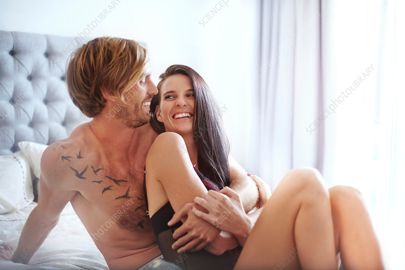 Couple laughing and hugging on bed