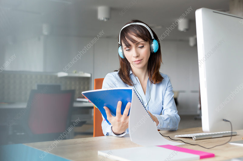 Businesswoman reading report at computer