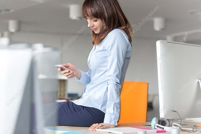 Brunette businesswoman texting on desk