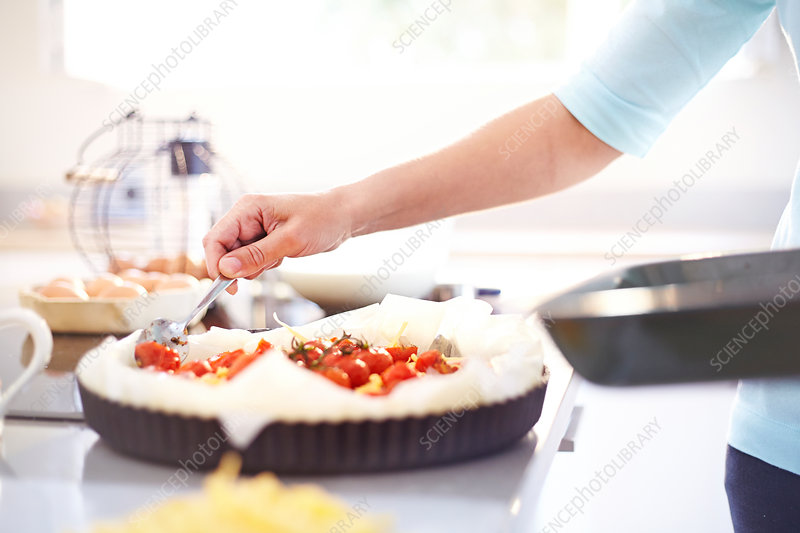 Woman preparing tomato quiche in kitchen