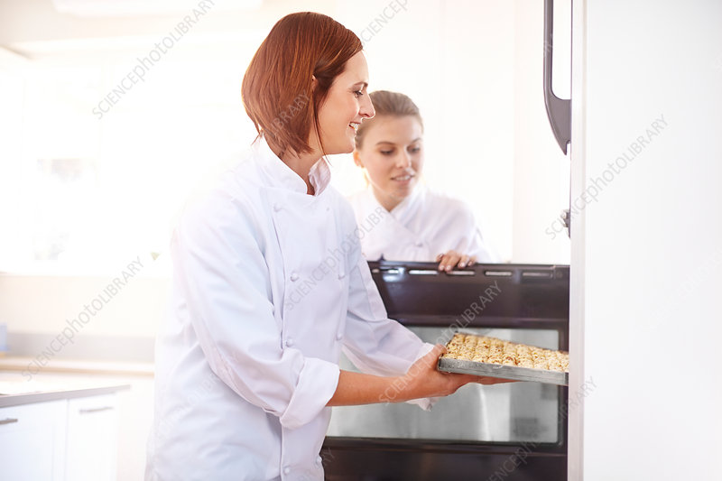 Chefs placing tray in oven