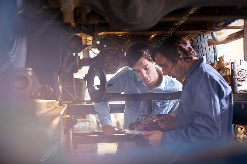 Mechanic and customer under car