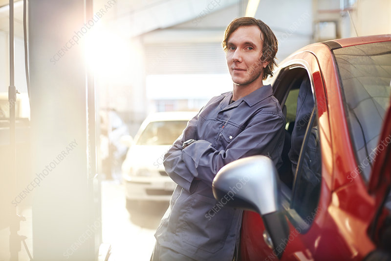 Mechanic leaning on car