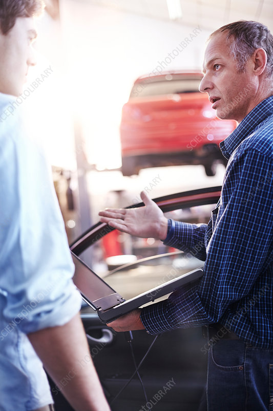 Mechanic with laptop talking to customer