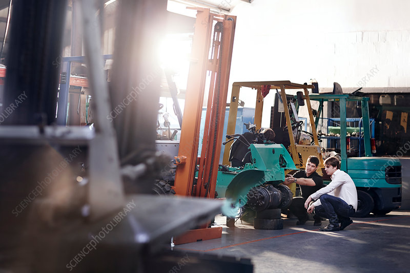 Mechanics fixing forklift