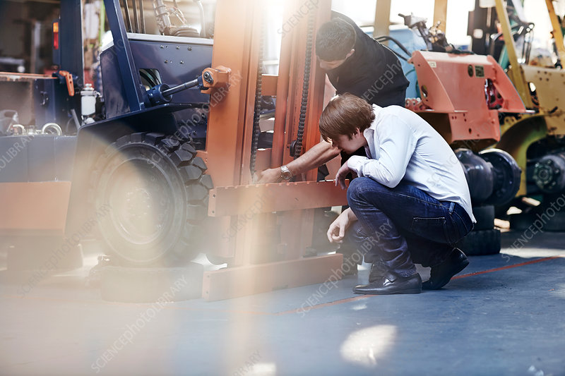 Mechanic and customer examining forklift
