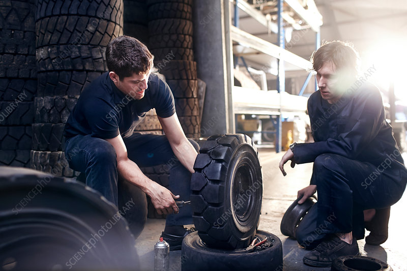 Mechanics fixing tire in auto repair shop