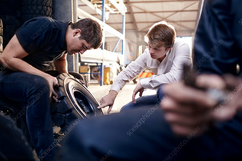 Mechanic and customer examining tire
