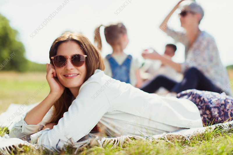 Woman laying on blanket in sunny field