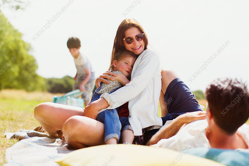 Family relaxing on blanket in sunny field
