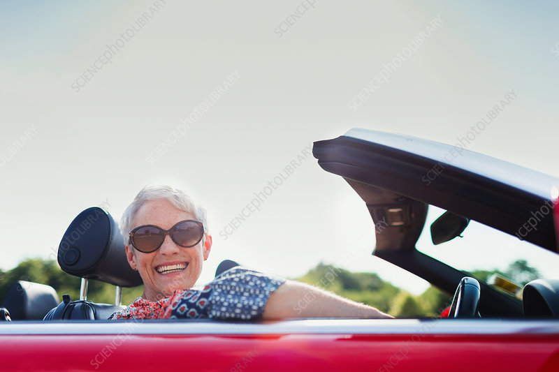Portrait senior woman driving convertible