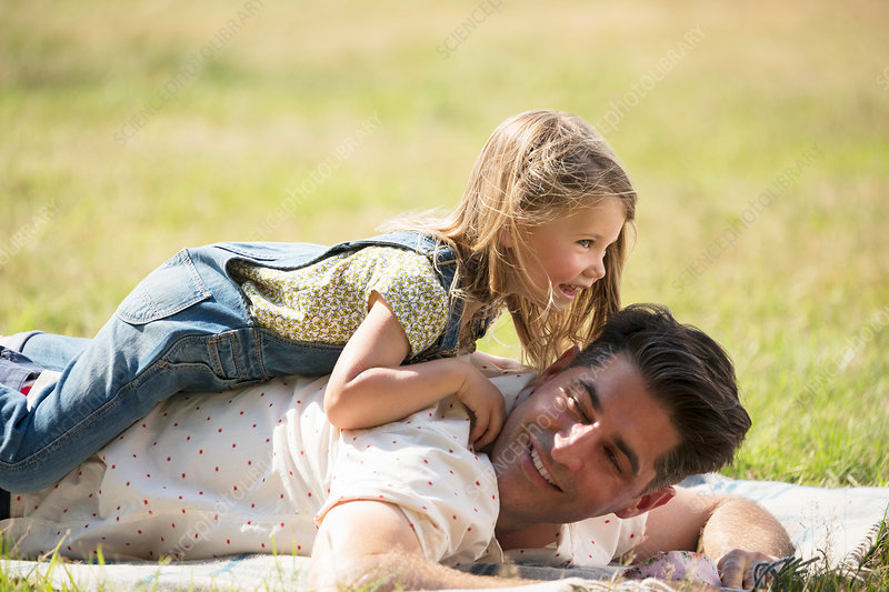 Playful daughter laying on top of father