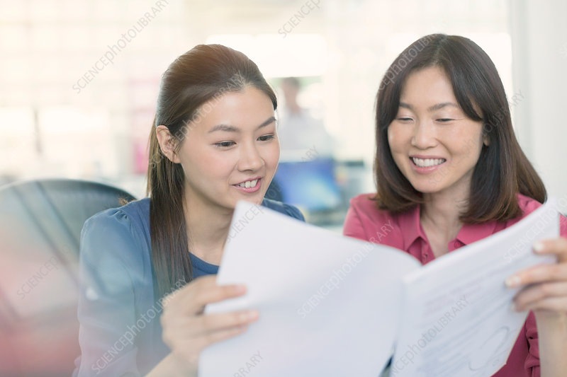 Businesswomen discussing paperwork