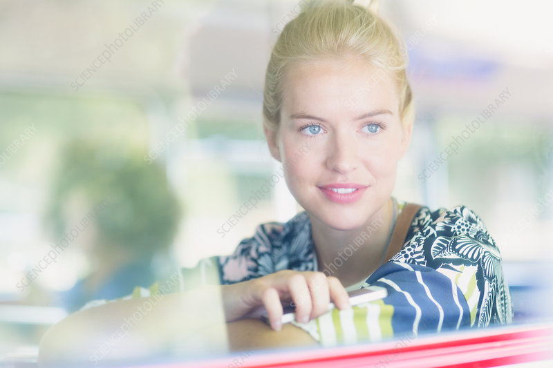 Blonde woman looking out window on bus