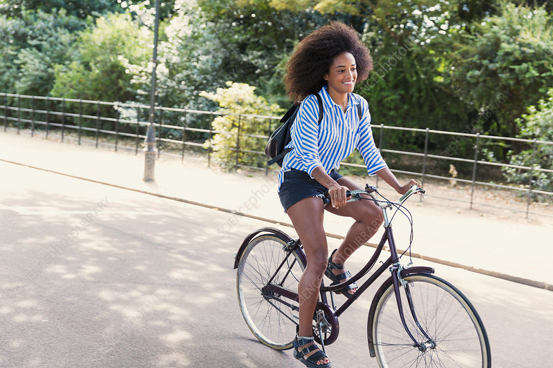 Woman with afro riding bicycle in park