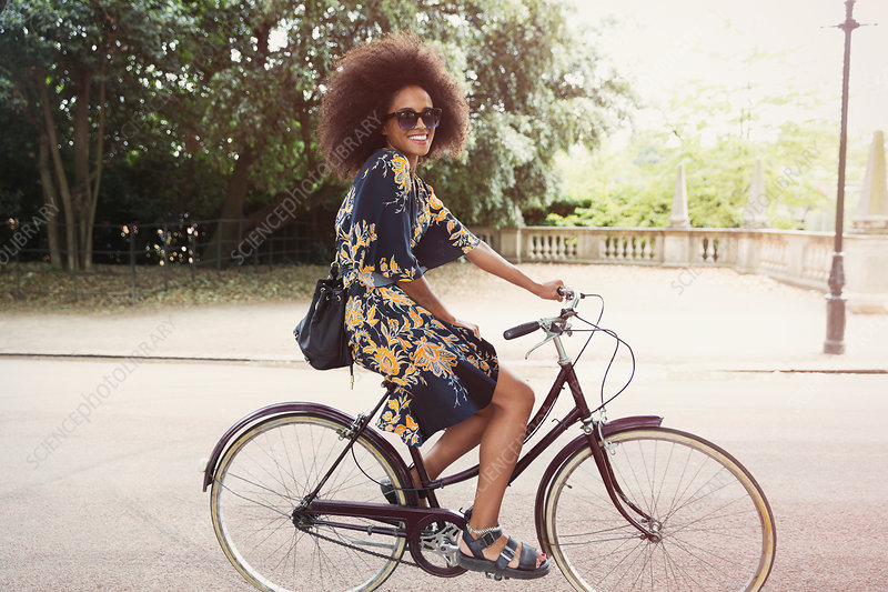 Woman with afro riding bicycle