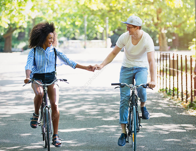 Couple holding hands riding bicycles