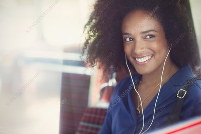 Woman with afro listening to music on bus