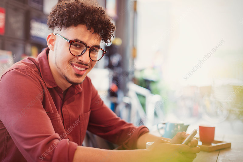 Man with curly black hair texting