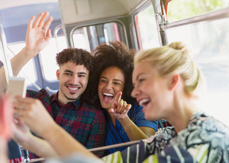 Enthusiastic friends taking selfie on bus