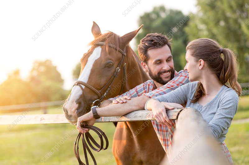 Couple with horse talking fence