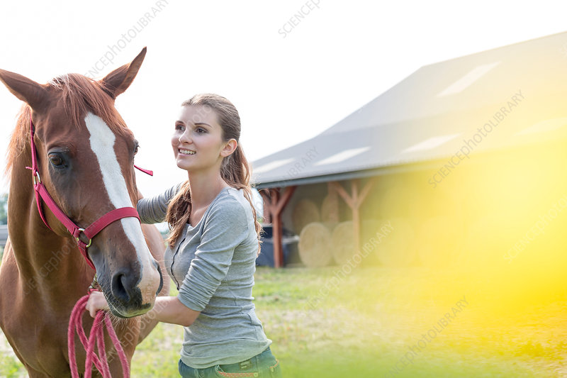 Woman with horse outside rural barn