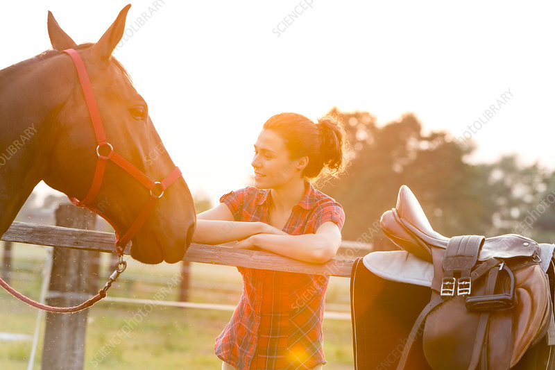 Woman looking at horse fence