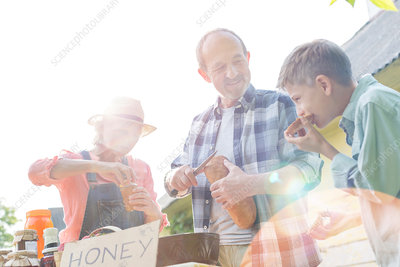 Grandparents and grandson selling honey